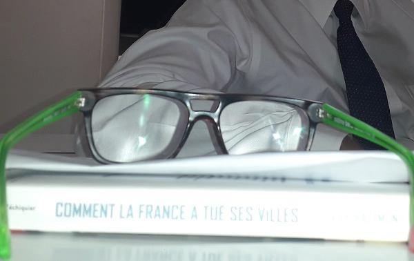 Pourquoi Yan Monplaisir porte-il des lunettes jaune et noir écaille, avec des tiges vertes et un point rouge ?